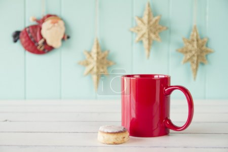 A red mug on a white wooden table. On the background Santa Claus flies between gold stars on a turquoise wooden wainscot. Christmas vintage style.
