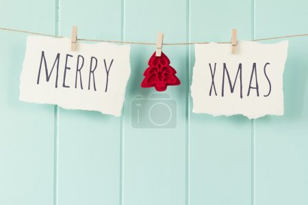 """Merry xmas"" and a felt tree hanging on a rope with clothespins. A robin egg blue wainscot as background. Vintage Style."