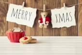 Příjemné vánoční scéna: červený misku s nějakou pečiva na bílý dřevěný stůl. Veselé Vánoce a medvídek s Santa Claus šaty visí na laně s clothespins. Vintage styl