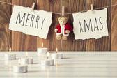 Příjemné vánoční scéna: svíčky na bílý dřevěný stůl. Veselé Vánoce a medvídek s Santa Claus šaty visí na laně s clothespins. Vintage styl