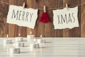 Příjemné vánoční scéna: svíčky na bílý dřevěný stůl. Veselé Vánoce a plstěnou stromu visí na laně s clothespins. Vintage styl