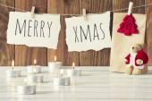 Příjemné vánoční scéna: svíčky, dar a medvídek s Santa Claus šaty na bílý dřevěný stůl. Veselé Vánoce visí na laně s clothespins. Vintage styl