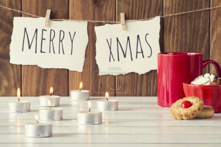 "Christmas cozy scene: candles, a red mug and a bowl with some shortbread on a white wooden table. ""Merry xmas"" is hanging on a rope with clothespins. Vintage Style."