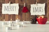 Příjemné vánoční scéna: svíčky, dva šiškami a červené mísa s nějakou pečiva na bílý dřevěný stůl. Veselé Vánoce a červenou plstí stromu visí na laně s clothespins. Vintage styl