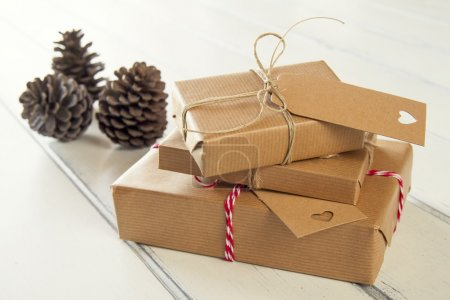 Some paper parcels wrapped tied with tags. Christmas gift boxes wrapped with paper kraft and tied with red & white baker's twine on a white wooden table. Vintage Style.