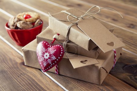 Some paper parcels wrapped tied with tags. A bowl with cookies, a red heart and some christmas gift boxes tied with red & white baker's twine on a white wooden table. Vintage Style.