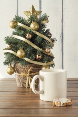 A christmas tree, a mug and a shortbread  on a wooden table. Vintage Style.