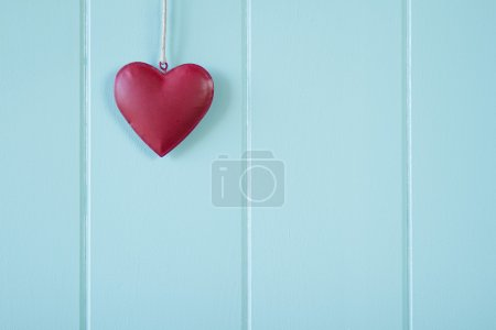 Valentine. A red heart on a turquoise wooden wainscot. Vintage.