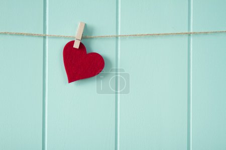 Valentine's day. A red heart hanging on a clothesline. A turquoise wooden wainscot as background. Vintage.