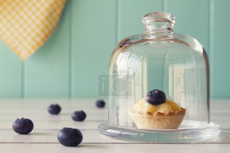 Tartlet with blueberries and pastry cream on a glass bell jar