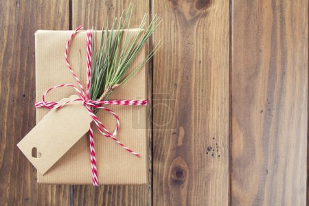 A paper parcel wrapped tied with a tag. A christmas gift box wrapped with paper kraft and tied with red & white baker's twine on a wooden table. Vintage Style.