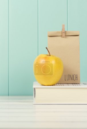 An apple and a paper bag with lunch on a book.