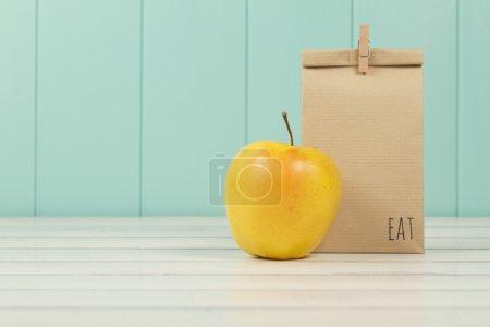 Une pomme et un sac en papier avec déjeuner