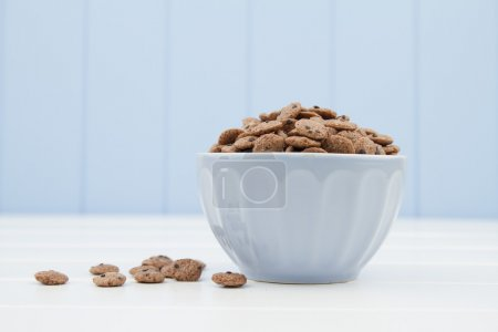 A blue bowl with cereals in the form of chocolate cookies on a white wooden table