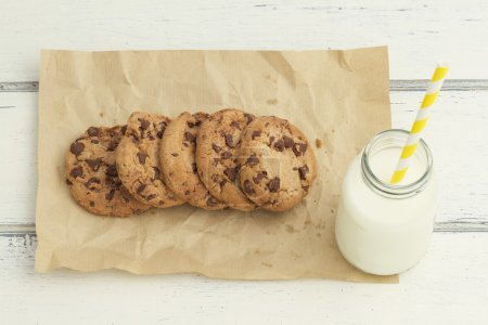 Some chocolate chip cookies and a school milk bottle