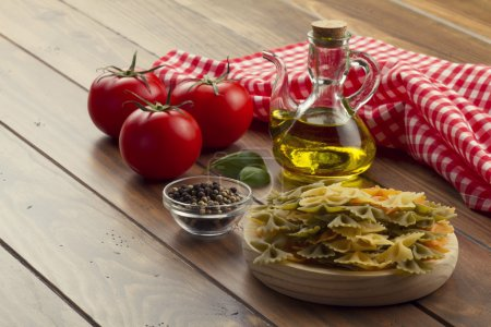 Some ingredients in a wooden table for cooking Italian pasta: tomatoes, farfalle, olive oil, peppermint and pepper. A checkered red napkin.