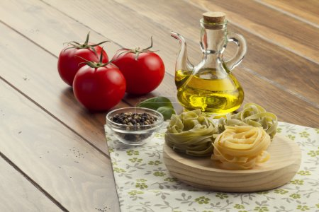 Some ingredients in a wooden table for cooking Italian pasta: tomatoes,  nests ribbons pasta, olive oil, peppermint, pepper and a napkin.