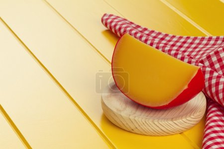 Edam cheese and a red checkered napkin on a yellow wooden table