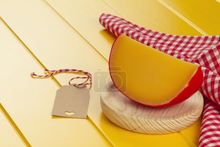 Edam cheese, a tag and a red checkered napkin on a yellow wooden table