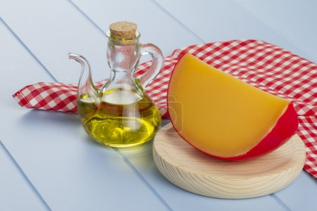 Edam cheese, a jar of olive oil and a red checkered napkin on a blue wooden table