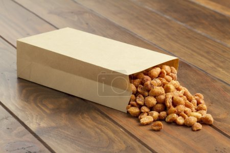 Some honey roasted peanuts in a paper bag on a wooden table