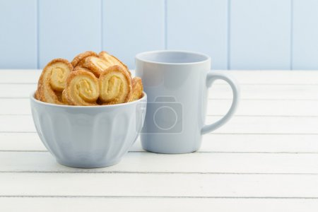 A blue mug and a bowl with puff pastry heart cookies on a white wooden table. A blue wainscot in the background.