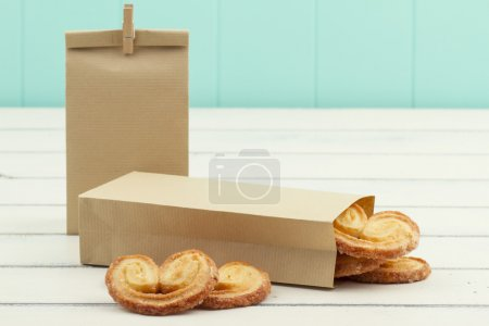 Paper bags with puff pastry heart cookies on a white wooden table. A turquoise wainscot in the background.