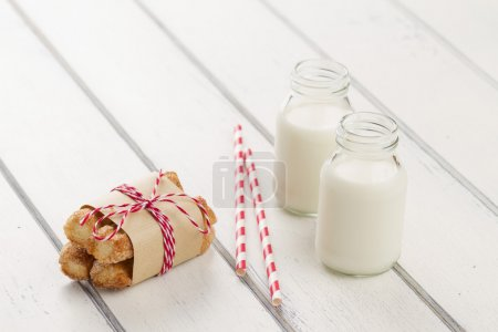 Puff pastry twists sprinkled with sugar with paper kraft and baker's twine red white. Two school milk bottles and two straw drink on a white wooden table
