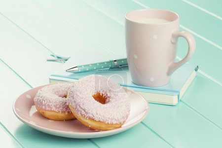 A break in the working day to eat two delicious strawberry doughnuts on a polka dots dish. A turquoise notebook, a ballpoint and a mug of milk.
