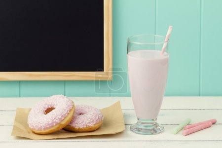 Two delicious strawberry doughnuts on a paper, a chalkboard, some chalks and a strawberry milkshake with a straw on a white wooden table