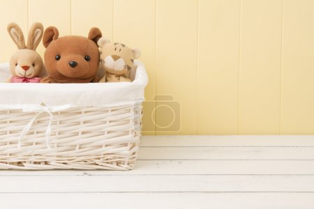 Stuffed animal toys in a basket on the floor.