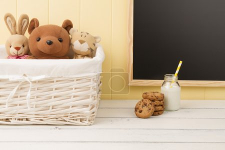 Some stuffed animal toys in a basket, chocolate chip cookies and a school milk bottle with a straw. A chalkboard in the background. Back to school.
