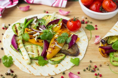 Photo for Tortilla and grilled vegetables - zucchini, eggplant, bell peppers, red onions, tomatoes and herbs - Royalty Free Image