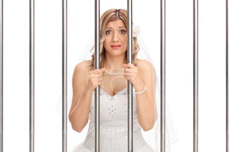 bride standing behind bars in jail