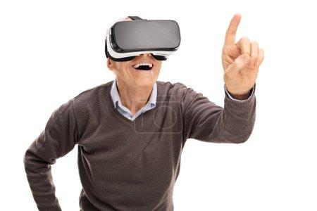 Photo pour Gentleman expérimentant la réalité virtuelle et atteignant à toucher quelque chose avec son doigt isolé sur fond blanc - image libre de droit