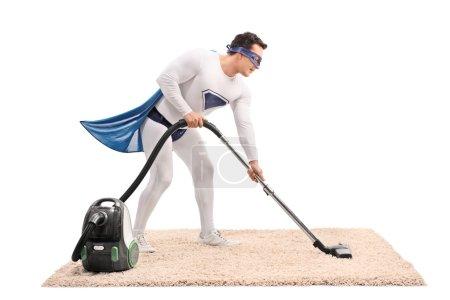 Young superhero vacuuming a carpet