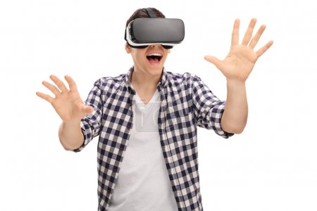Photo for Excited man experiencing virtual reality via VR headset and touching something with his hands isolated on white background - Royalty Free Image