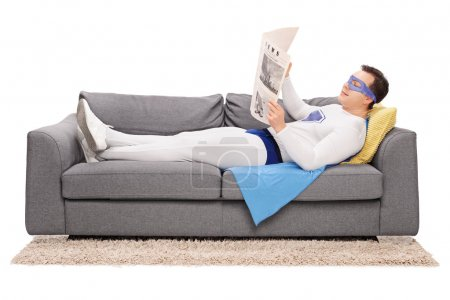 Photo pour Jeune super-héros détendu couché sur un canapé gris et lisant un journal isolé sur fond blanc - image libre de droit