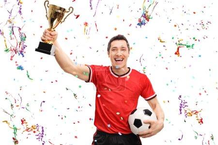 Joyful football player holding a trophy