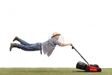 Mature man being pulled by a lawn mower