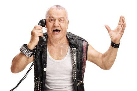 Photo pour Homme mûr dans une vieille veste punk parlant au téléphone et gesticulant avec ses mains isolées sur fond blanc - image libre de droit