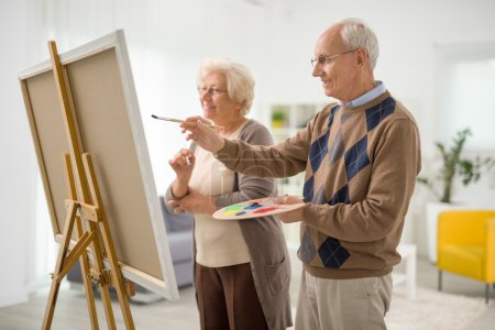 Photo for Older man and woman painting something on a canvas with paintbrushes at home - Royalty Free Image
