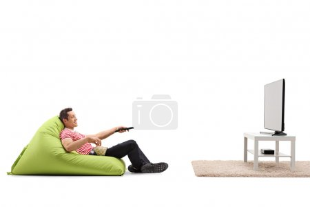 Photo for Relaxed man sitting on a comfortable green beanbag and watching TV isolated on white background - Royalty Free Image
