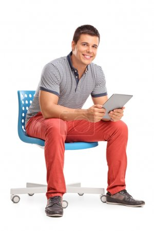 Photo for Vertical shot of a young man holding a tablet and sitting on a chair isolated on white background - Royalty Free Image