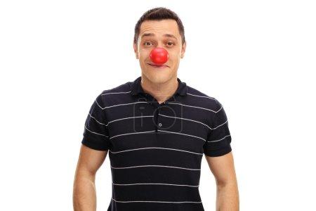 Photo pour Jeune homme posant avec un nez de clown rouge isolé sur fond blanc - image libre de droit