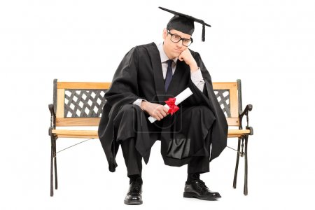 Photo for Angry college graduate holding a diploma isolated on white background - Royalty Free Image