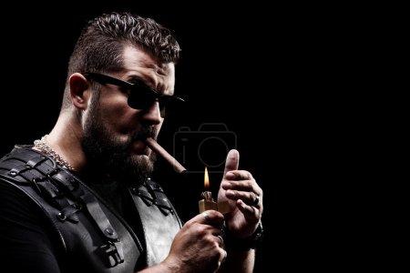 Badass biker lighting up a cigarette on black back...