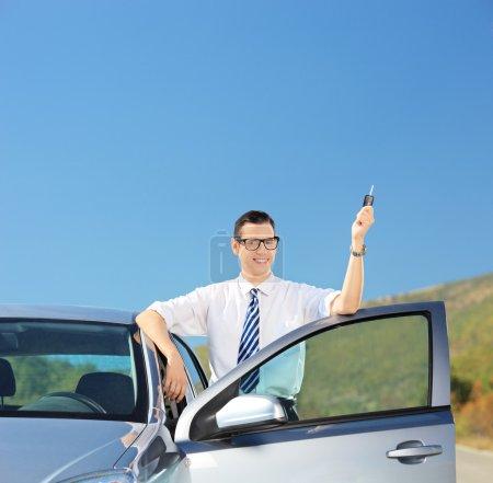 Man holding car key on road