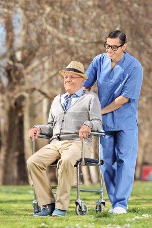 Photo pour Infirmière mâle poussant un aîné en fauteuil roulant en plein air par une journée ensoleillée - image libre de droit