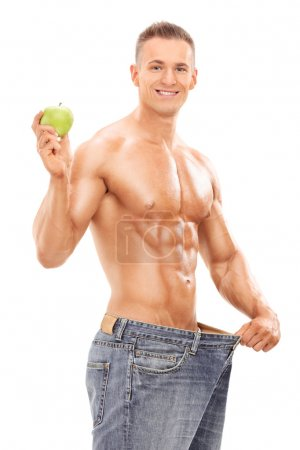 Man in oversized jeans holding apple